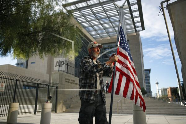 Supporter David Fleeman hangs a flag outside of the federal courthouse, Monday, Oct. 30, 2017, in Las Vegas. Jury selection is set to begin in Las Vegas for the long-awaited trial of Nevada cattleman and states' rights figure Cliven Bundy, two sons and on
