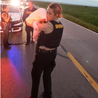 Pennington County Deputies Kelsey Schwartz and Kristina Weckman take turns caring for a crying young baby who is safe after a pursuit.