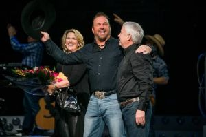 From left, Trisha Yearwood, Garth Brooks and Oilers Entertainment Group CEO Bob Nicholson celebrate the 5 millionth ticket sold on