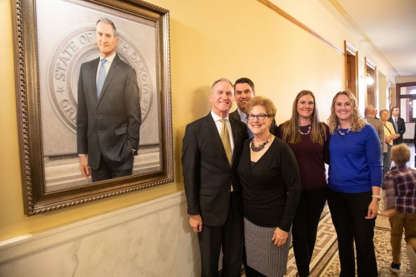 Governor Daugaard and family stand next to his portrait unveiled Tuesday in Pierre.