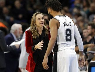 FILE - In this Dec. 26, 2017, file photo, San Antonio Spurs assistant coach Becky Hammon, left, talks with guard Patty Mills (8) during the second half of an NBA basketball game against the New York Nets, in San Antonio. A diversity report released shows