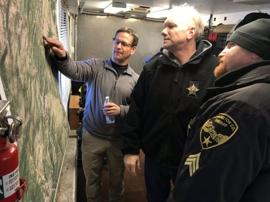 Rescue crews, including Pennington County Deputy Sheriff Willie Whelchel, look over a map of the search area Saturday.